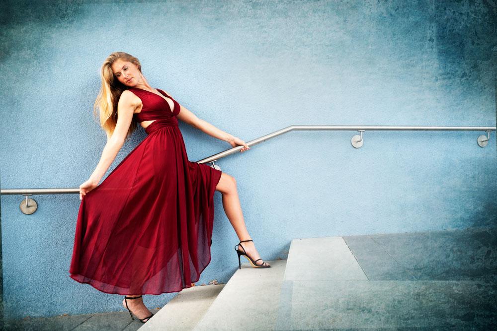 Junge Frau im roten Kleid vor blauer Wand