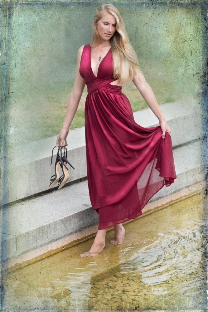 Junge Frau im roten Kleid barfuß im Wasser